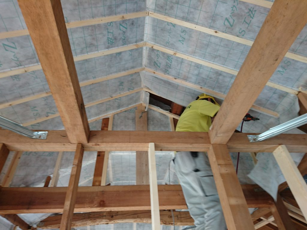 断熱は新聞紙のリサイクル品のセルロースファイバーを採用。屋根面の室内側も丁寧に紙張りをしていきます。